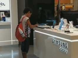 A Boy with No Computer Uses Tablet at Store to do Homework