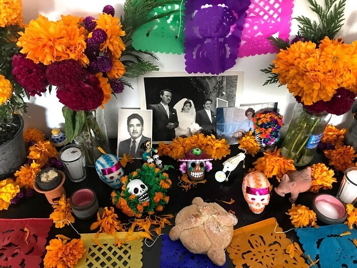 Pictures of the deceased family members are displayed at altar